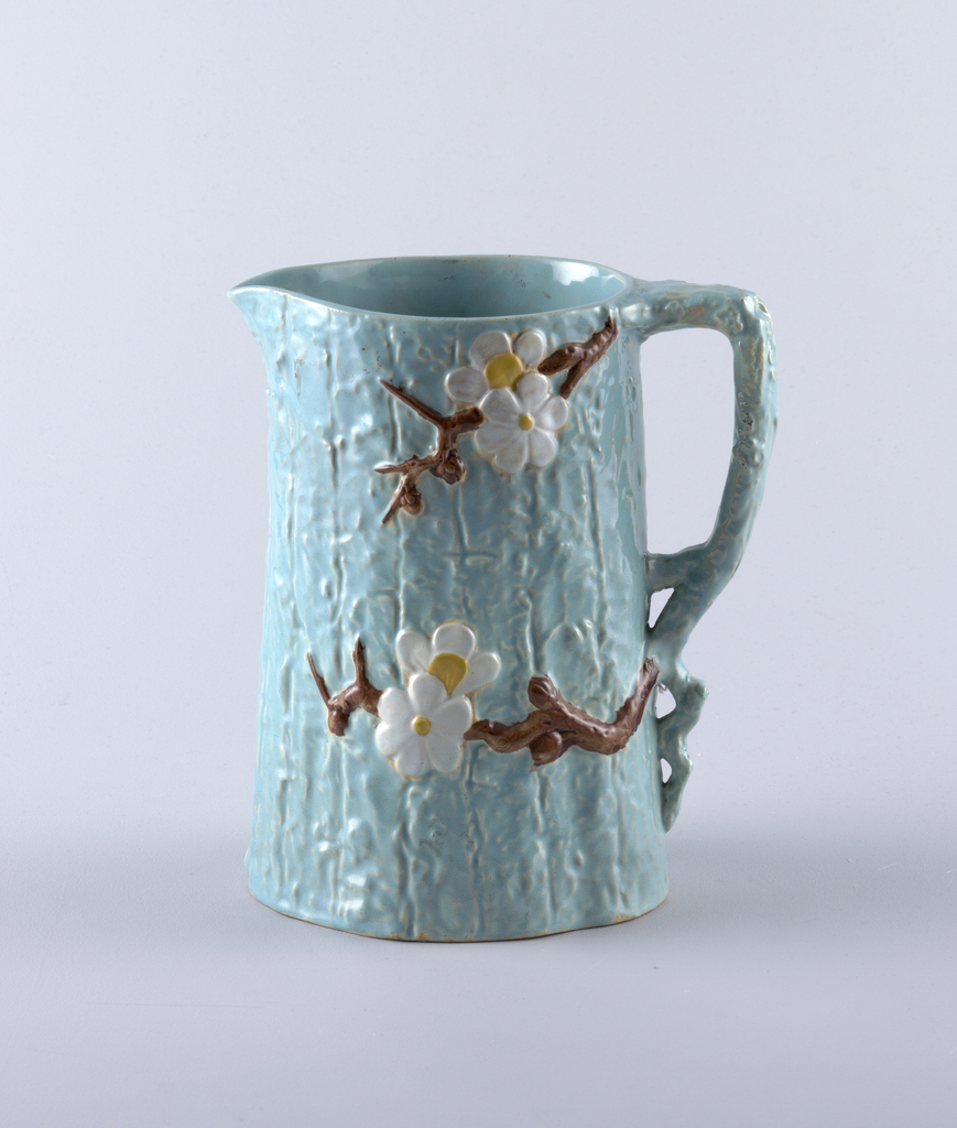 Tall picture with oval section. Molded exterior to resemble tree trunk with prunus branch and blossoms. Glazed pale blue interior and exterior. Handle in the form of a gnarled branch.