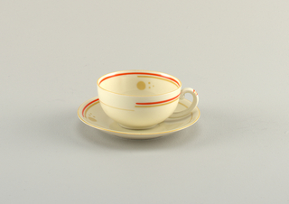 Round cup and saucer with light orange line of glaze at rim and partial circle of bright orange glaze within.