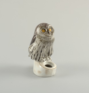 In the form of an owl perched on a tree trunk with circular opening for ink well.