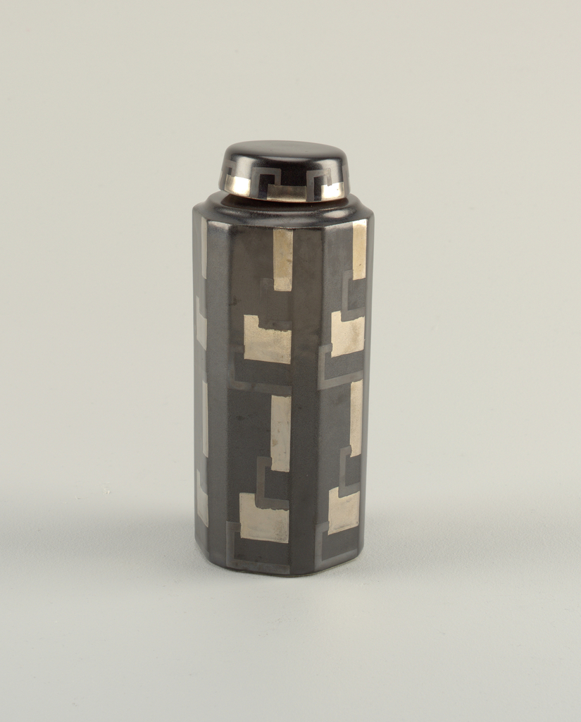 Tall hexagonal form decorated in a semi-matte black finish with pewter colored squares and dark grey lines that form squares with pewter sections.  Rounded lid with similar decoration.