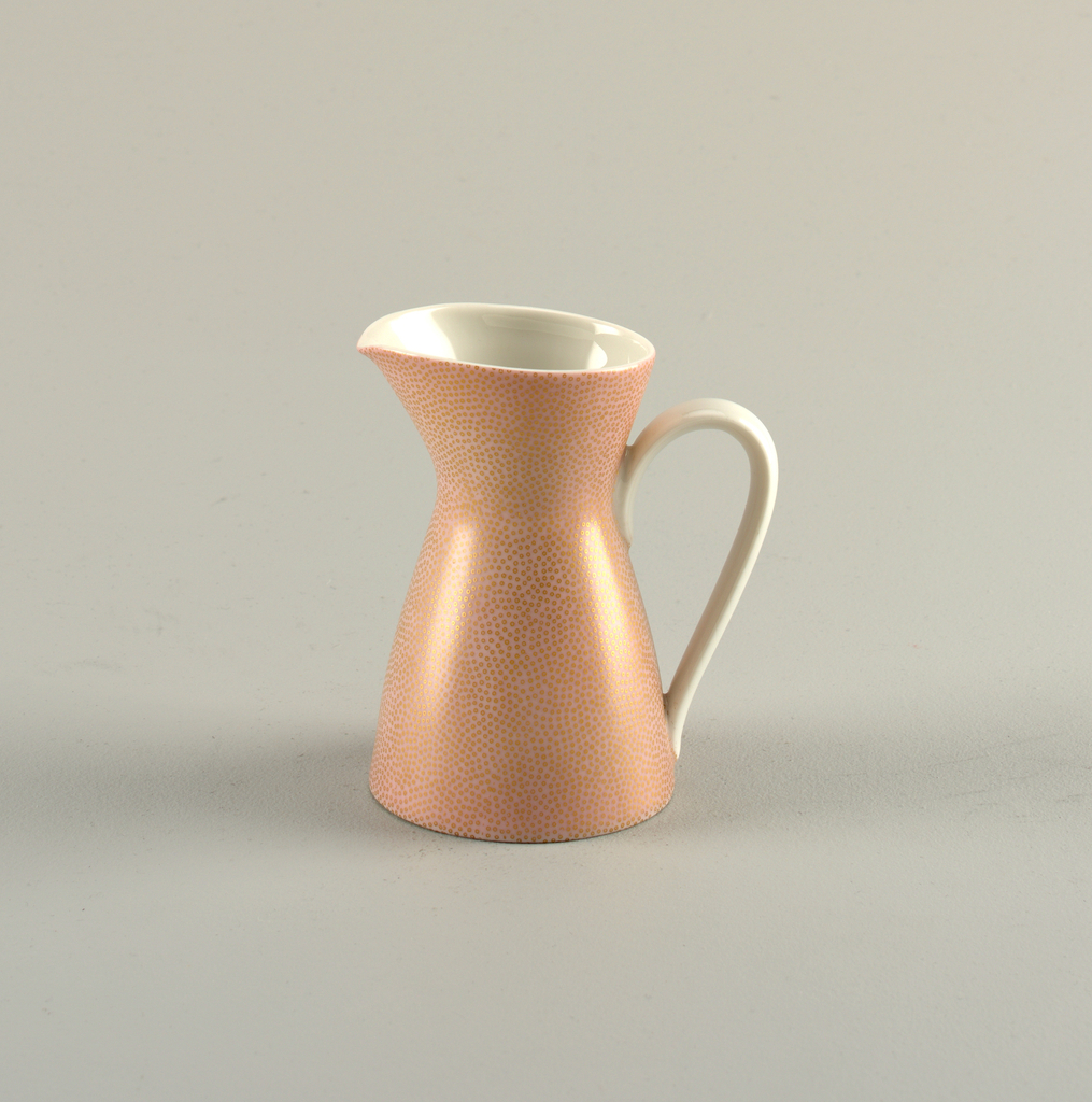 Body of roughly hour glass form; pink-glazed ground with tiny gilded irregular circles; circular mouth with spout; large white loop handle opposite; white-glazed interior.