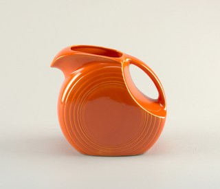 Red disc-shaped pitcher with series of concentric circles molded at edges; mouth angled back, transitioning into curved handle; small circular spout.