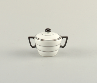 White porcelain sugar bowl and lid with thin black bands circling the body; two black handles. Lid has black concentric circles and black spherical knob.