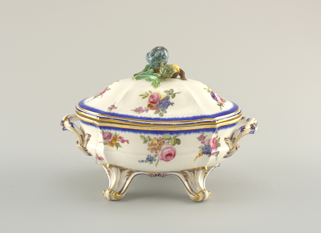 Four-footed tureen with lid having handle of vegetables in relief.  The body and lid with white ground decorated with flowers and blue bands at edges; decoration heightened by gilding at legs, handles and edges if body and lid.