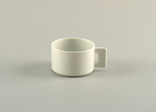 Squat, thin-walled cylindrical cup with flat, squared handle having narrow recatangular piercing near wall of cup; white glaze.