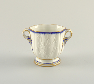 Curved and shaped bowls, slightly flaring, on cavetto feet. Loop handles ending in leaves. Plum blossom relief on sides. Edges and leaf-forms on and below handles decorated with blue peigné and gold.