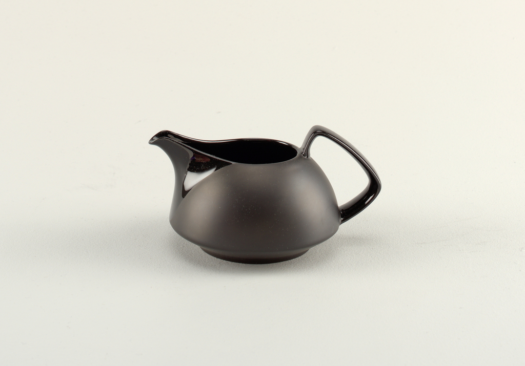Black low, rounded pitcher; flat base. Angular handle and open glazed spout.