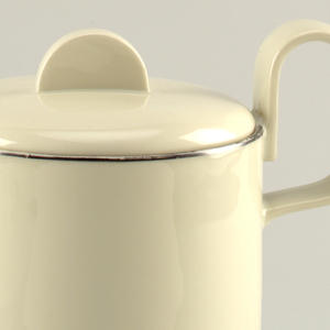 "Creamy-grey porcelain body. Coffee pot (a)  is cylindrical in shape, with curved lower section that tapers to circular foot. Spout is upright, with curved and cylindrical, attached along the entire length of the spout. Handle is placed high on body, formed like upright reversed ""U."" Cover (b) is slightly domed, fitted with flange for closure, with flat semi-circular upright finial. Platinum band painted around lip and spout."