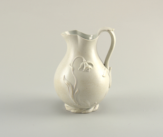 Stoneware jug with molded decoration.