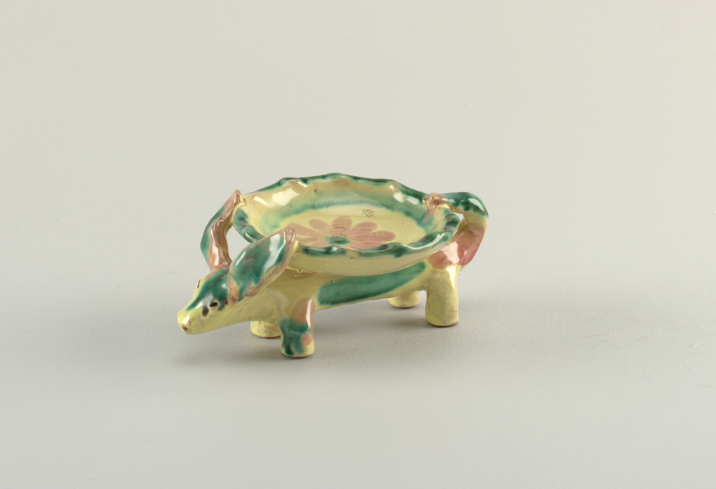 Round shallow bowl with ridged edge and glazed flower at center, held on the back of a quadruped with long ears. Running yellow, green and pink glaze.