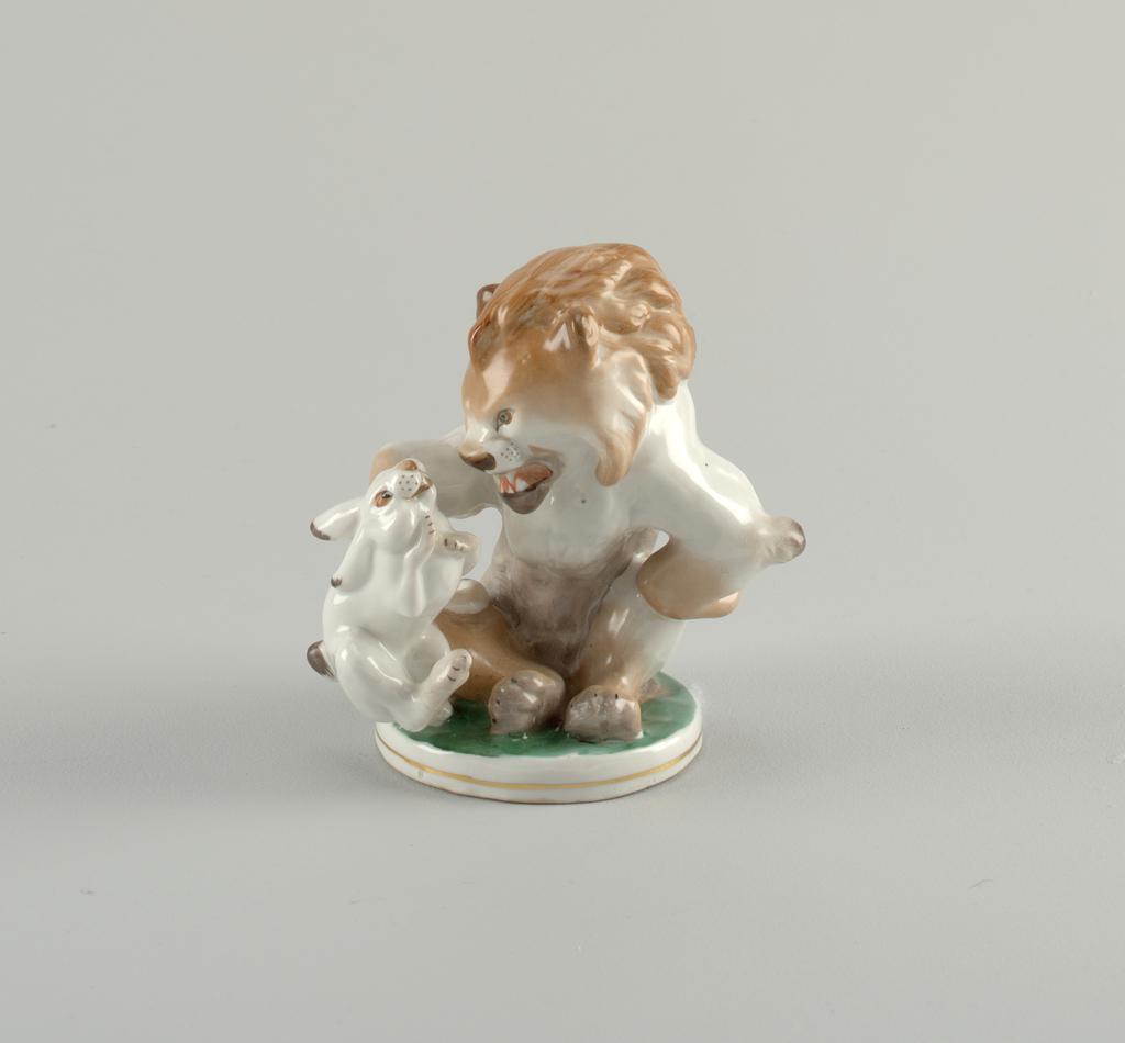 Sitting lion holds small rabbit at shoulder; circular base.