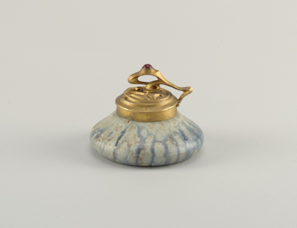 """(a) Circular stoneware body with spreading base and conically tapered uppersection. Glazed grey-green with irregular striations of blue, semi-matte surface, numerous small pits. Underside with foot rim abraded to reveal body. Hinged cover of gilt bronze with circular lip rim, domed cover with symmetrical relief """"whiplash"""" curves. Thumbpiece in extended curve rising over domed center with applied red cabochon glass jewel. (b) clear glass well liner, cylindrical and plain. The body (a) of the inkwell has a circular spreading base, with a conicallytapered upper section creating a flattened dome shape. The body is appar-ently thrown on the wheel. The exterior is glazed in a semi-matte grey- green, with irregular striations of grey-blue. The surface of the glaze shows numerous pits. The underside of the base is unglazed. The body is fitted with a hinged neck ring, and attached swinging cover of gilded bronze. The domed cover to the well is decorated with raised elongated """"whiplash"""" curve motifs arranged symmetrically. A metal thumbpiece con- tinues the mount, rising in a curve over the dome, and applied with a red cabochon of stone or paste. Interior of inkwell, is fitted with a glass liner (b) of cylindrical, flat-bottomed shape."""