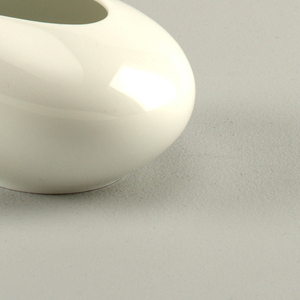 Sugar bowl in teardrop form, streamlined with elongated spout, meant to be held from body.