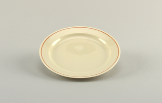 Molded creamy-grey porcelain body. Flat circular plate with flat slightly upturned rim. Red line around edge of rim.