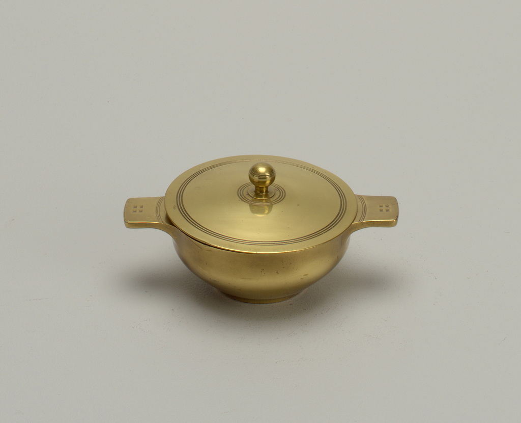 Circular bowl (a) with incurved lower section. Flat base. Molded flange handles with engraved transverse lines and four stylized rectangles. Flat cover (b) with bezel. Two sets of concentric rings engraved on surface. Brass ball finial.