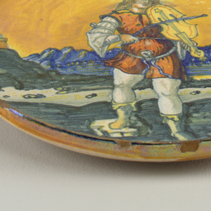 Maiolica dish with image of a man with a hat playing a violin in a landscape with a yellow sky. Iridescent overglaze luster.