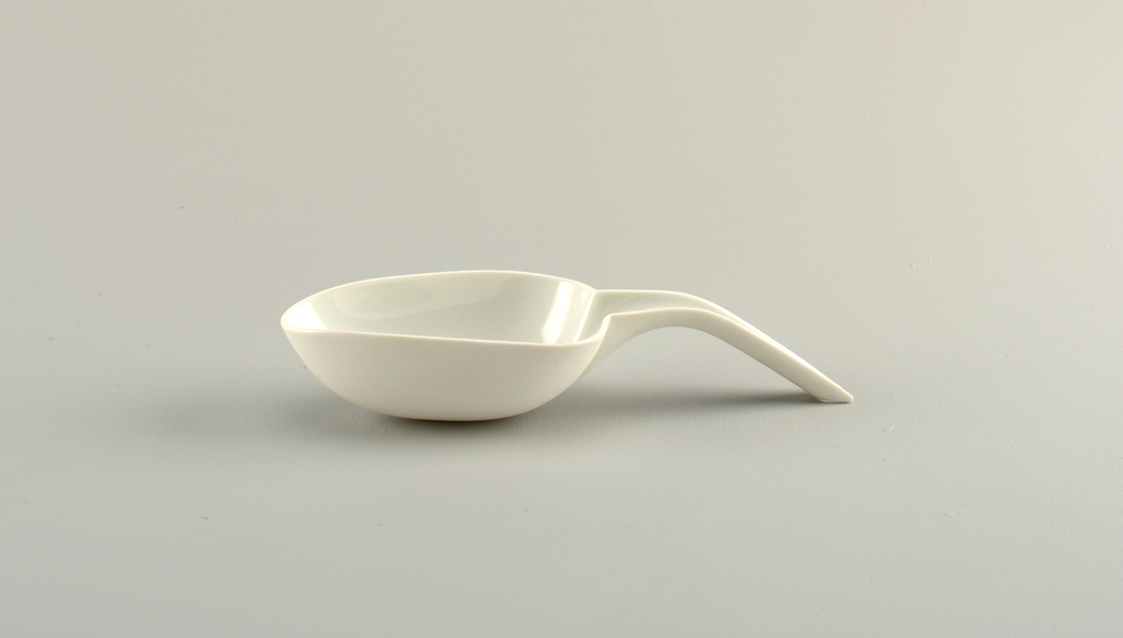 White porcelain body. Molded, spoon shaped, oval and tapered bowl which incurved rounded base; at wide end and rim, an integral downward curved semi-cylindrical handle. Outer end of handle, cut at angle to provide support for bowl. Reverse with triangular molded joint between handle and bowl.