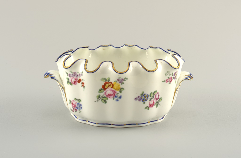 Crenellated glass cooler with floral garlands on white ground.