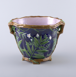 Round cachepot, sides tapered toward base. Base and upper edge molded with browm-glazed bamboo motifs. Base with four feet; lip molding at sides to form handle, with bamboo moldings connecting lip and base. Outer body glazed deep blue, molded with raised foliage in green and with flowers in white. Interior and underside of base glazed bright pink-mauve.