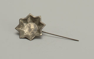Stamped eight-pointed star with flat circular center. A wire skewer is soldered to the back.