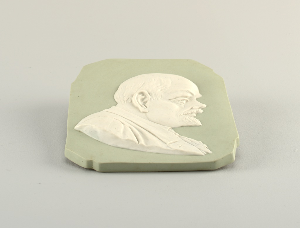 Rectangular with irregular corners, greenish background, white bust of Lenin in profile in relief