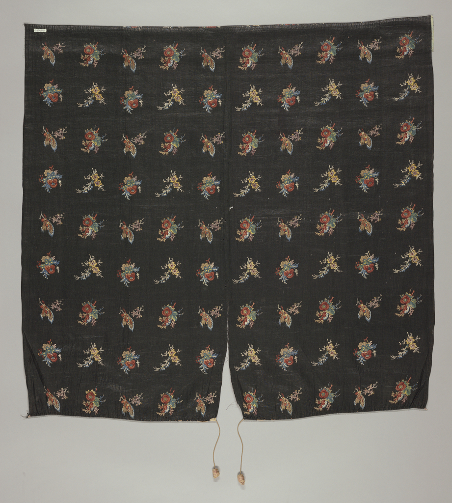 Black grazed percale printed in poylchrome design of detached floral sprays in rows. Four different bouquets in repeat. One width (two selvages present) hemmed and lined at bottom, gathered on to drawstring with silk tassels at top showing that this is half of a petticoat.