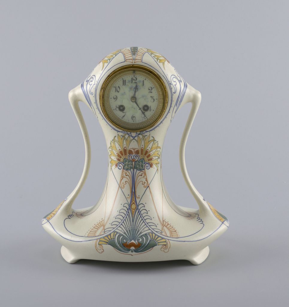 Curved clock with double handles and rounded edges; decorated with symmetrical floral and line motifs in yellow, red-orange, and blue on cream background. Face of clock lightly decorated with floral arrangement of violet calla lilies.