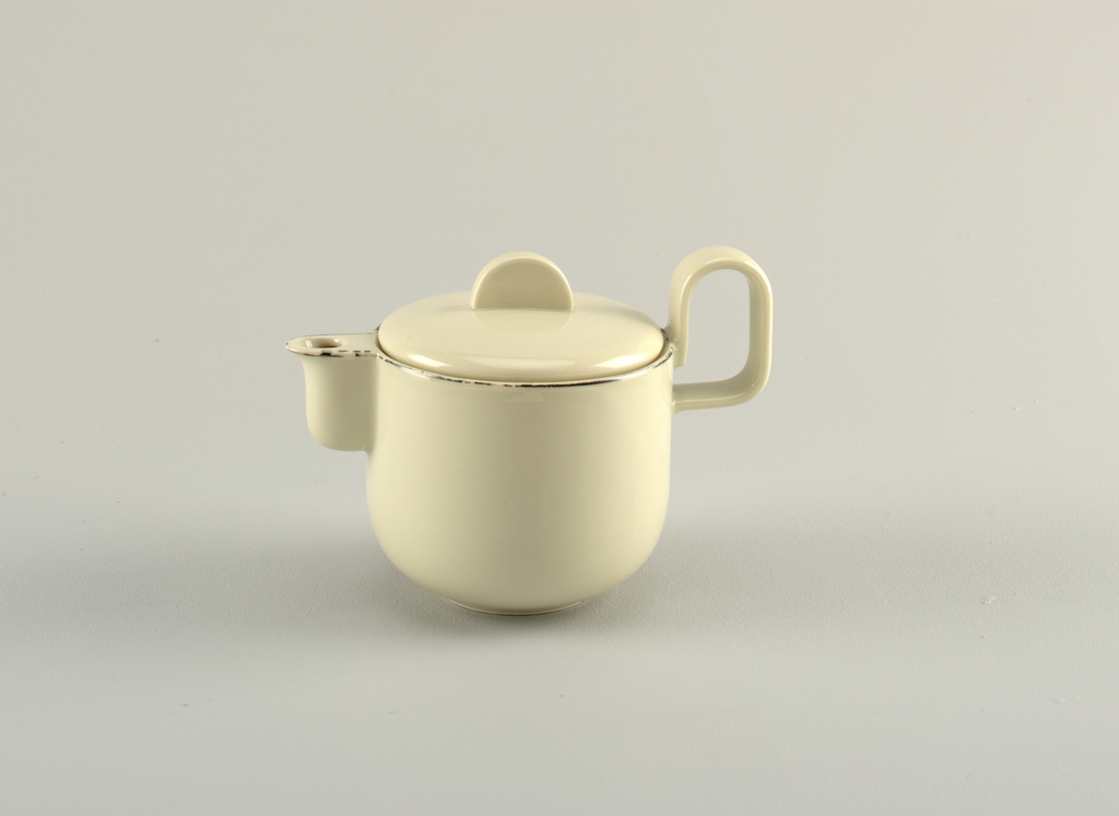"""Creamy-grey porcelain body. (a) Milk jug is cylindrical in shape, with curved lower section that tapers to circular foot. Spout is upright, curved and cylindrical, attached along the entire length of the spout. Handle is placed high on body, formed like upright reversed """"U."""" (b) Cover is slightly domed, fitted with flange for closure, with flat semi-circular upright finial. Platinum band painted around lip and spout."""