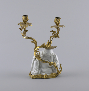 """Seated figure (""""laughing buddha"""") in glazed white porcelain with a swirling, leafy, bifurcated ormolu branch terminating in two candle sockets."""