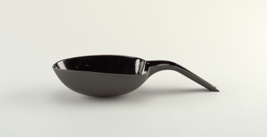 Black porcelain body. Molded, spoon shaped, oval and tapered bowl which incurved rounded base; at wide end and rim, an integral downward curved semi-cylindrical handle. Outer end of handle, cut at angle to provide support for bowl. Reverse with triangular molded joint between handle and bowl.