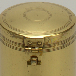 Cylindrical body, flat base. Rivet-held hinge with slightly domed cover. Strap closure and open pin for securing. Series of three engraved concentric bands near base, at rim, lower cover, and on top. Tinned interior.