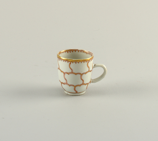 Cup with handle. Decorated in red and gold, in outline of conventionalized petals. In center of saucer, and at interior of cup is a butterfly.