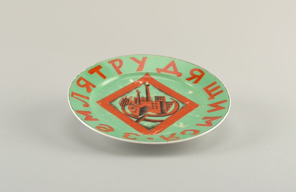 "Circular, green ground with red lettering and image; in the center a lozenge with sickle, wheat sheaf, stylized factory; around the border the slogan in Russian, ""Land for the Working People."""