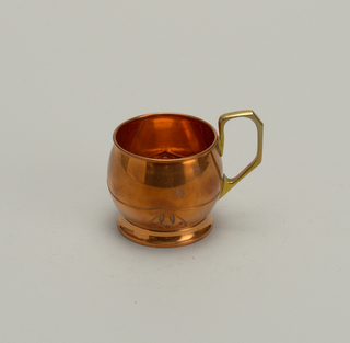 Copper mug on a ring foot with small interlace trefoil. Angular bass handle rising above rim.