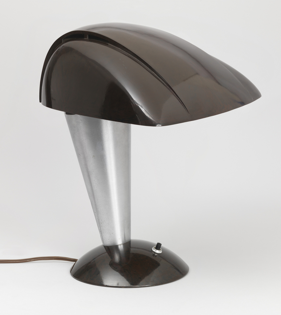 Sloping trapezoidal Bakelite shade mounted on angled inverted cone-shaped aluminum shaft on domed black Bakelite base with cylindrical metal switch at front; underside of shade covered with cellulose film panel.