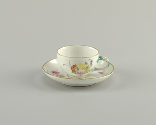 Cup has double-curved side, cylindrical foot, intertwined twig handle touched with green. Saucer flat, with steeply-curved side and gilded edge. Cup and saucer decorated with scattered flowers and floral sprays.