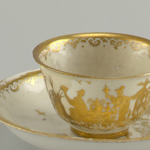 Bell-shaped cup, flat saucer with curved sides and ring foot. Engraved gilt chinoiserie decoration of figures, birds, trees and scrolls.