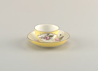 Cup with simple loop handle; saucer deep, with curved sides. Inside of cup and saucer white, with scattered flowers; outside of cup underside of rim of saucer yellow, with white reserve panels, on cup, in which are flowers.  Edges of cup and saucer brown.