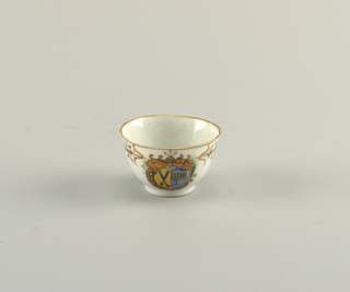 Export armorial tea bowl. Painted armorial featuring arrows, within a scrollwork cartouche. Floral decoration. Gilding at rim.