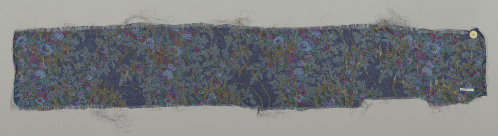 Sample of sheer dark blue-colored silk with a multicolored print of four vertical columns formed by solidly massed small-scale flowers. Over this, a design of scrolling lines, circles and irregular lozenges brocaded in metallic gold thread. Both selvedges present.