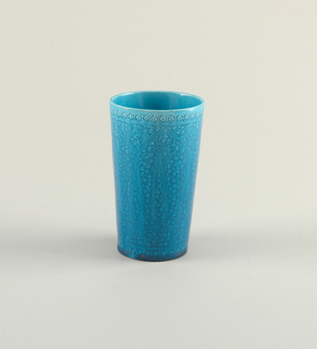 An earthenware beaker in a rich blue glaze. This piece has a floral like pattern around the top, and a similar pattern below.