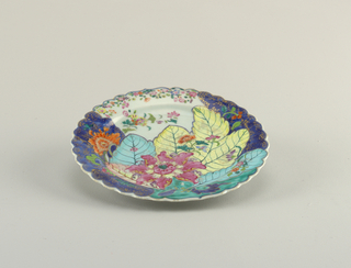 "Circular plate, concave center, scalloped rim. Upper surface painted in ""Tobacco Leaf"" pattern in pink, yellow, blue, with underglaze blue areas and gilded details. Reverse painted with underglaze blue and red floral sprigs."