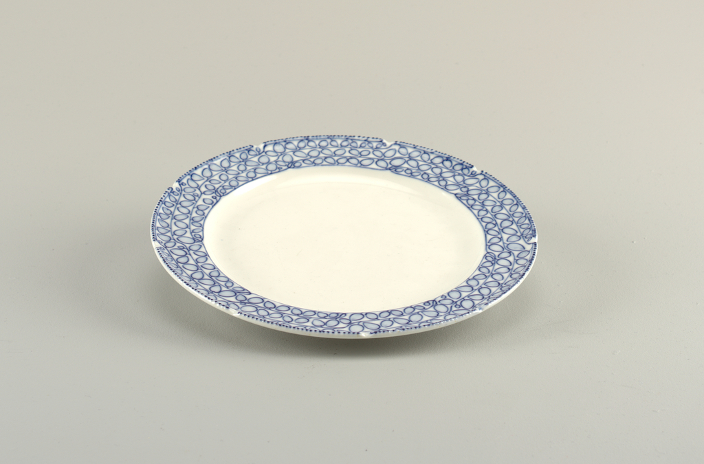 Circular form featuring overall abstract, leafy vine pattern on border in underglaze blue on white ground; lip of plate's perimeter raised and curved slightly inwards; raised dot pattern in blue on edge alternately puncuated by small white indentations; plate's central reserve undecorated.