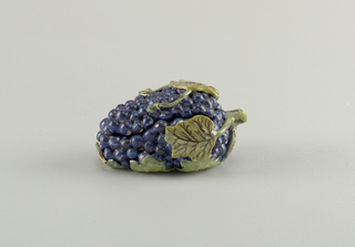 Tureen in the form of a grape cluster with leaves. The fruit is glazed a dark indigo. Green leaves are reticulated with brown veins.