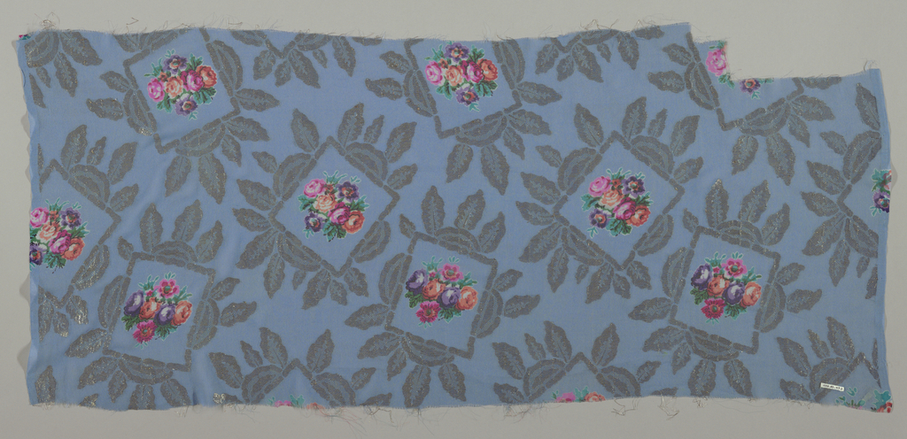 Sample of solid light blue georgette crepe with silver brocaded leafy frames containing a small-scale bouquet of roses printed in multicolor. Both selvedges present.