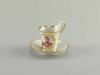 Battle of Waterloo commemorative cup with concave sides, with greatest diameter at lip. Flat strap handle. Flat saucer, horizontal ogee marly. Cup has bust portraits of Arthur Wellesley, 1st Duke of Wellington and Gebhard Leberecht von Blücher, encircled by gold palm and laurel branches. Saucer has gold inscription: Sieger / bei La belle Alliance / 1815 (Winners, the Beautiful Alliance).