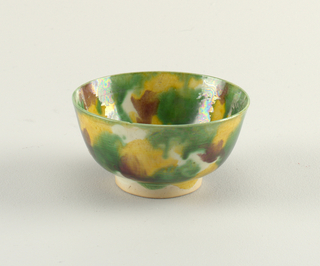 Deep bowls on band foot with sides flaring slightly outward, mottled green, grown and yellow glaze. Each base of bowl has underglaze double line in blue with underglaze mark, prinked in black.