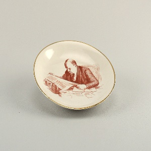 """Circular, with image of Lenin sitting at desk reading copy of """"Pravda"""" newspaper; thin gilded band at edge"""