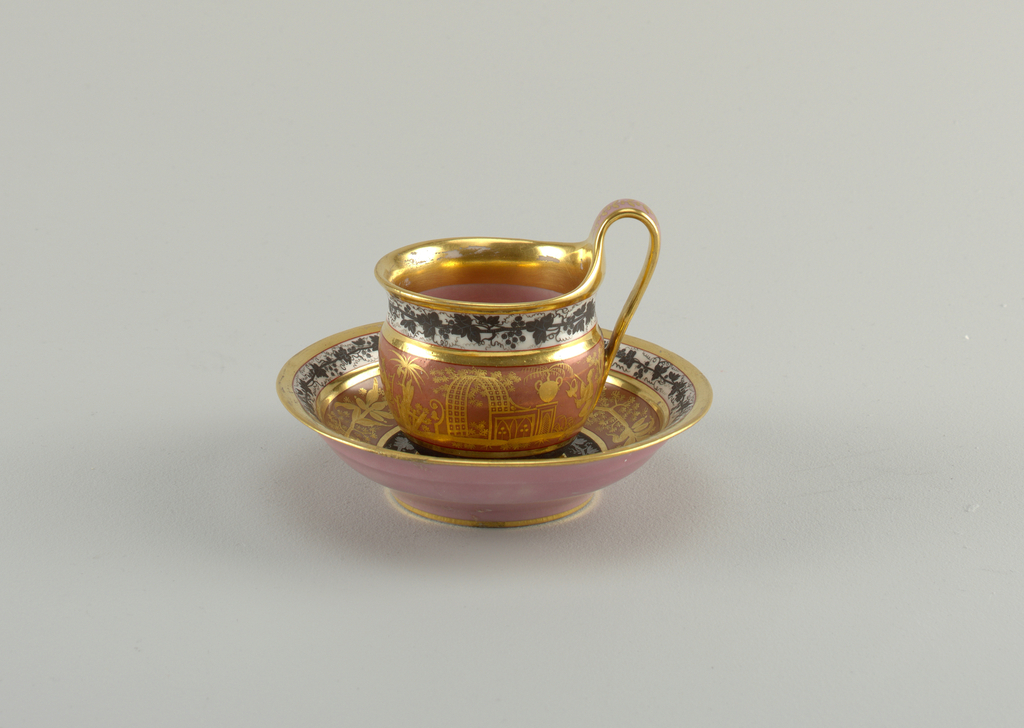 Curved cup with cavetto neck and high loop handle. Curved saucer. Overglaze decoration on cup: at bottom, silver vine on black band; center: pink with gold chinoiserie; top: black vine on white. Inside pink, with wide gold band. Saucer with similar decoration, but wreath instead of chinoiserie.