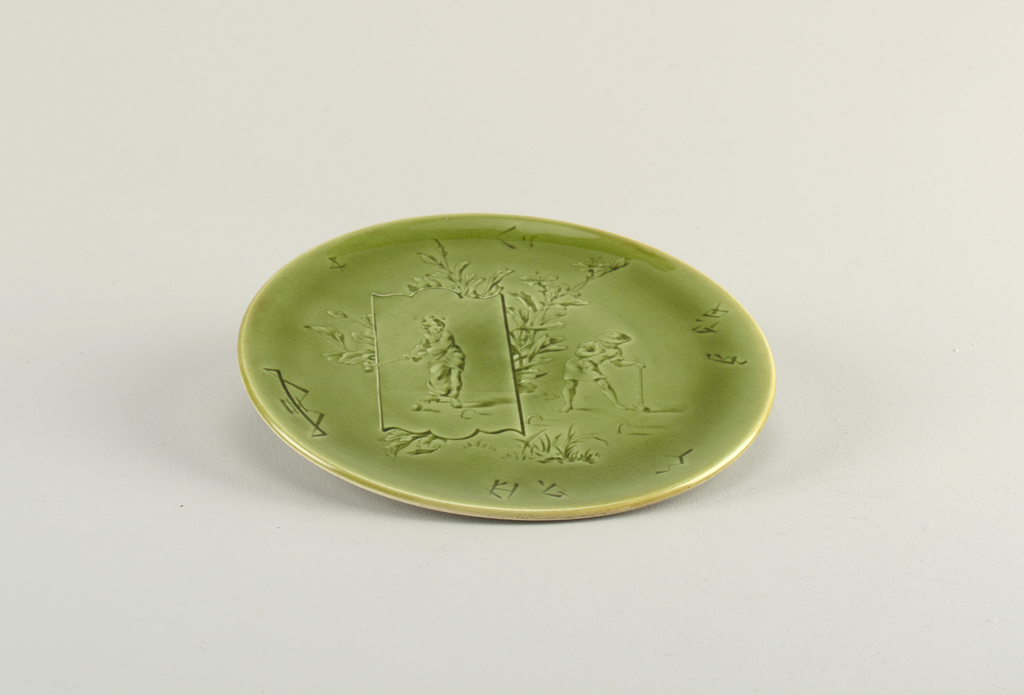 A green glazed circular porcelain plate depicting a young couple playing croquette with flowers in the background.